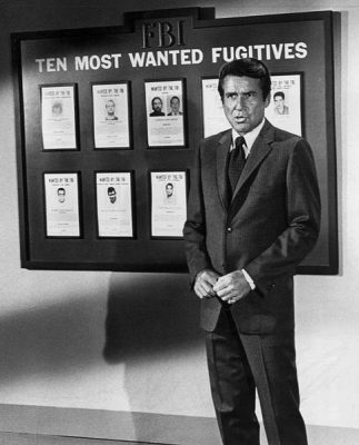 Efrem Zimbalist junior posing in front of the ten most wanted list