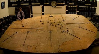 A large tabletop map in a war room with toy tanks and soldiers